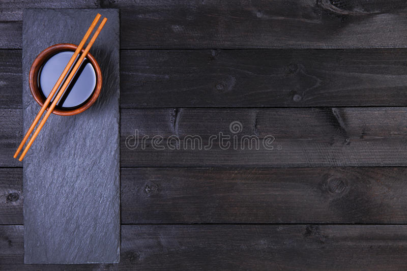 Background for sushi. Soy sauce, chopsticks on black table. Top view with copy space stock photography