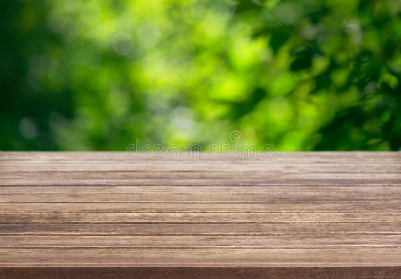 Wooden table surface and blurred leaves of a tree in the background stock photo