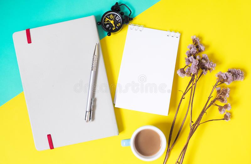 Background templates with blank text space on note paper of book and decorative dried flowers, alarm clock And coffee mugs stock photo