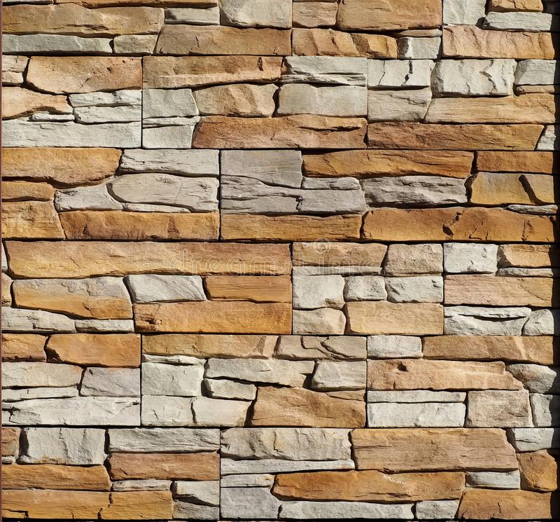 Background and texture. Brown and gray wall made of embossed natural stones blocks royalty free stock photography
