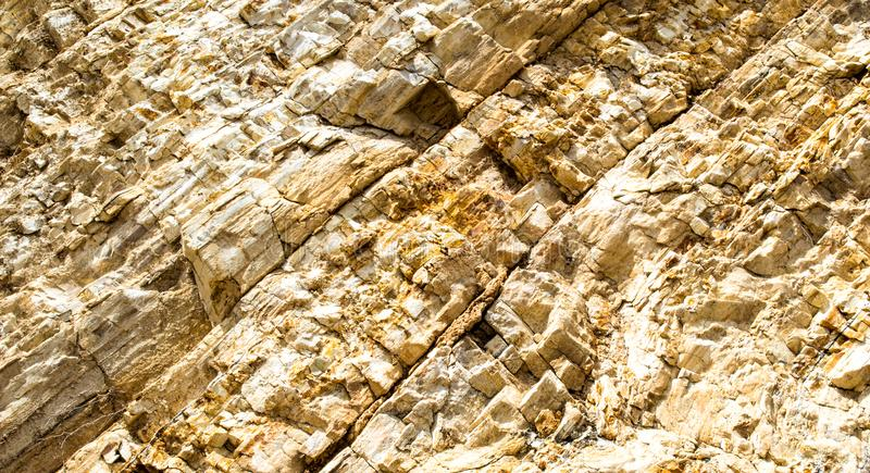 Background texture colorful jagged rock wall. Background texture close up of colorful jagged rock wall with crevasses on a beach in California stock image