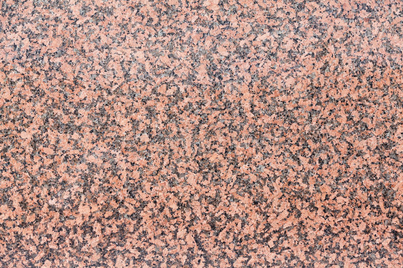 Background texture of deep pink granite in a polished slab. Background texture of deep pink granite stone in a polished slab with copy space suitable for royalty free stock photography