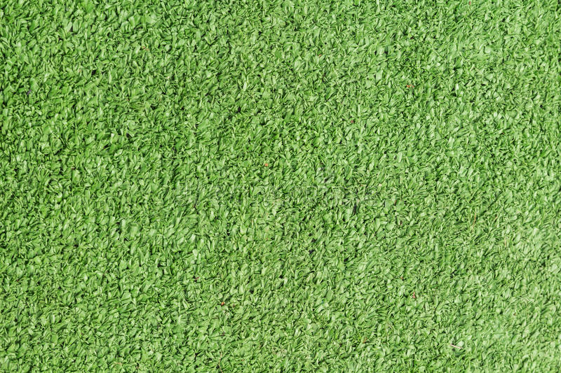 Background texture with fake grass. In a public children playground, top view stock images