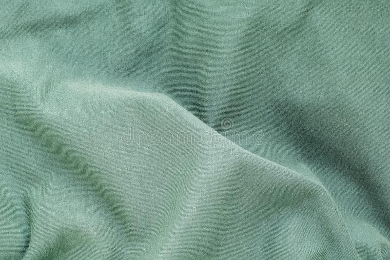 The background texture is a green soft wavy fabric, top view, close-up. royalty free stock images