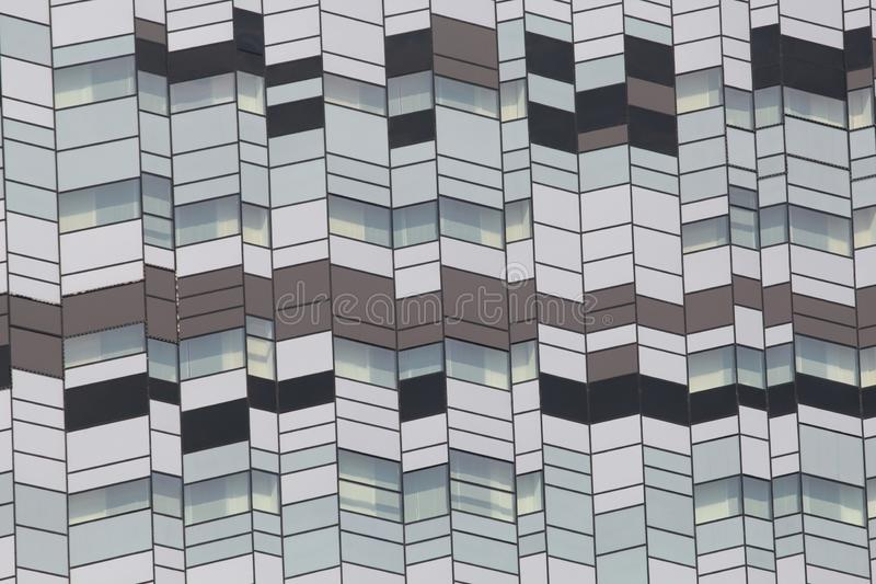 Background texture of a modern architecture skyscraper`s facade with symmetrical light and dark grey glass windows. Background texture of a modern architecture royalty free stock photos