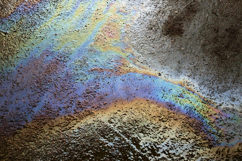 Background texture of an oil spill on road. Environmental pollution stock photography