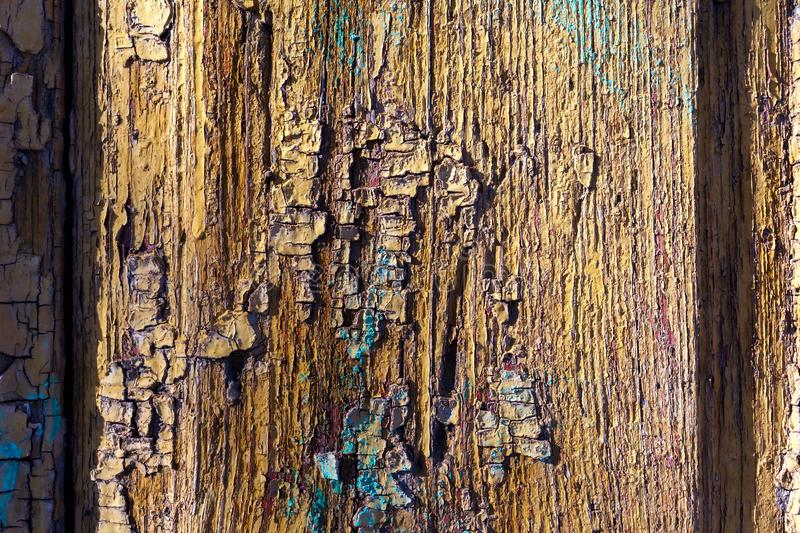 Wooden colorful texture background an old painted wood surface with flaky yellow, purple, blue and brown paint stock photos