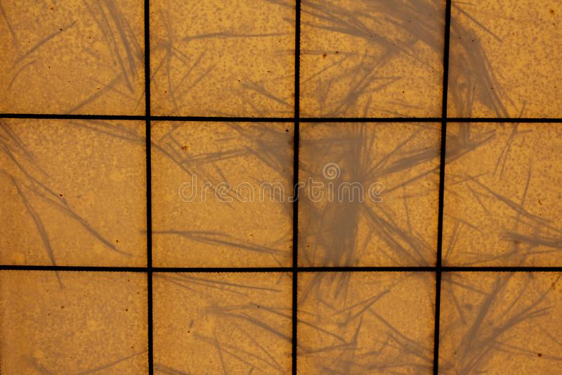Background texture pattern made of dark metal wires and yellow tarpaulin with pine needles on top all shaped like yellow tiles. Background texture pattern made stock images