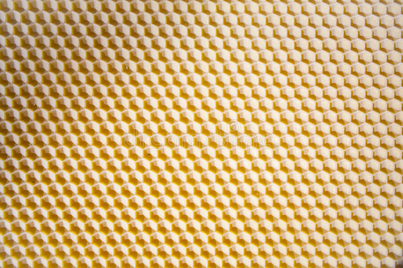 Background texture and pattern of a section of wax honeycomb. From a bee hive filled with golden honey in a full frame view royalty free stock image
