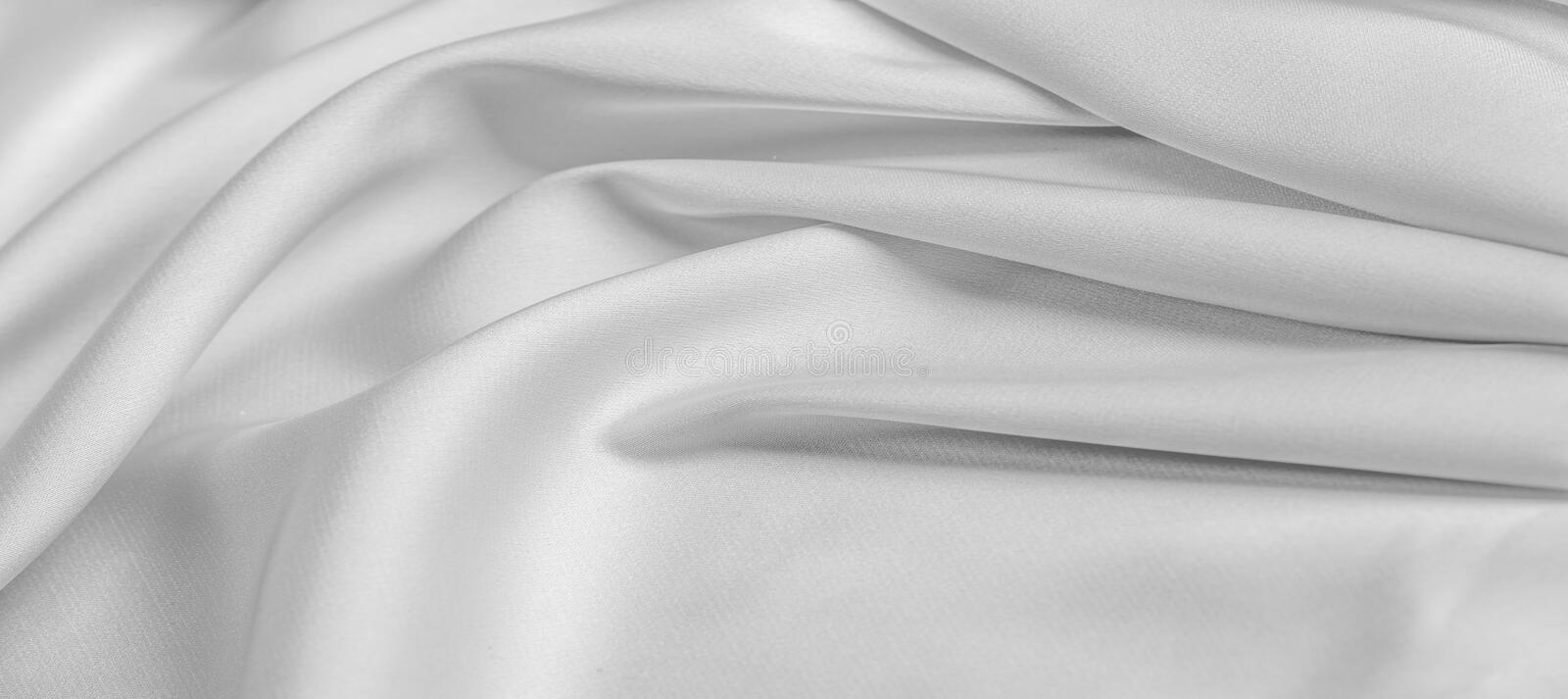 Background texture, pattern. White silk fabric. It has a smooth matte finish and gets its strength from slightly twisted yarns. royalty free stock photography
