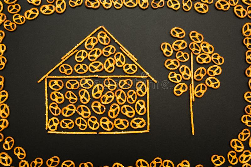 Background texture of salted pretzels and mini sticks in the shape of a house and a tree on a black background stock photos