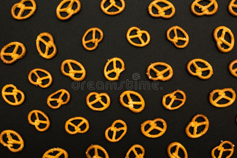 Background texture of salted savory mini pretzels in the traditional looped knot shape on the black background stock photo