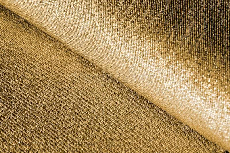 Background texture of shiny golden glitter bokeh. bright festive textile Christmas background. Glittering pearly yellow texture. Gold surface with holiday royalty free stock image