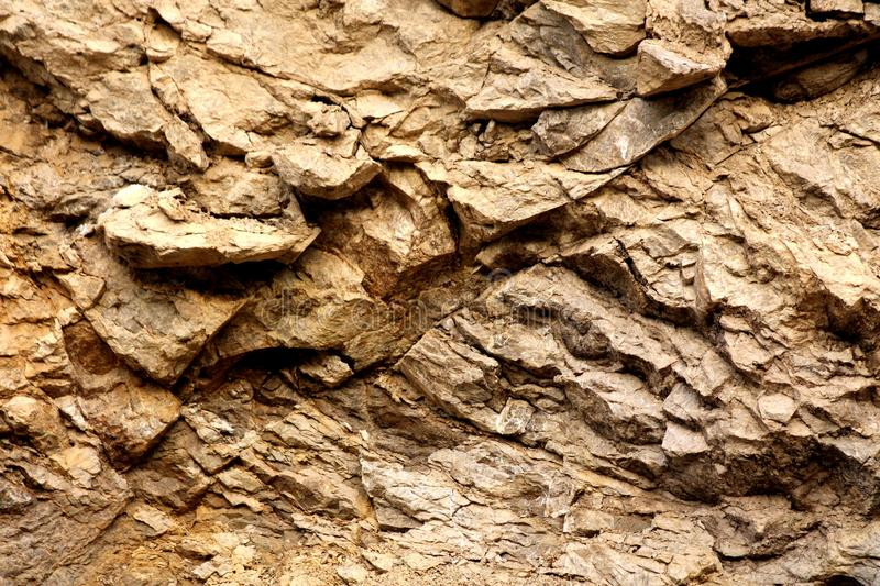 Background texture wallpaper of light brown to yellow stone formation mixed with wet dirt royalty free stock photography