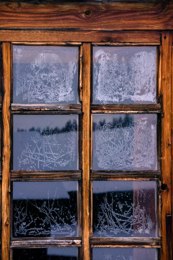 Frosty pattern on the glass. Background, texture - wintage window frame with frozen glass with frosty patterns stock image