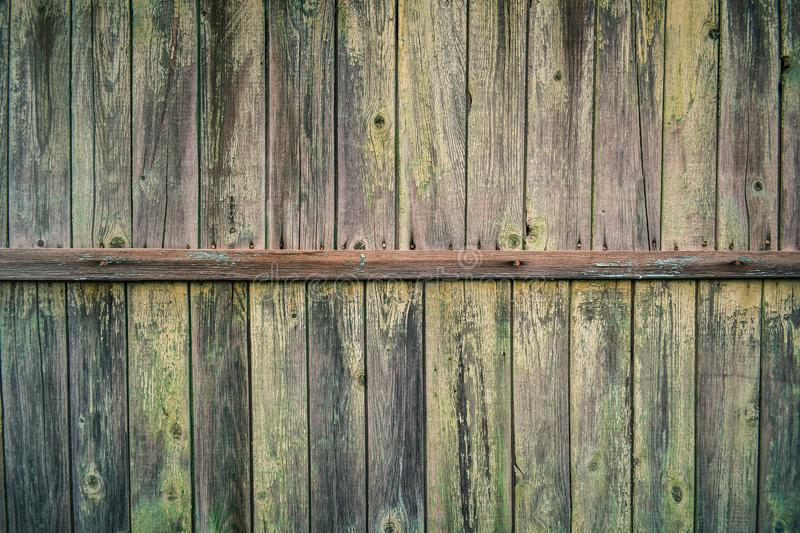Background with the texture of the wooden wall. Of old wood with peeling paint. vintage texture of an old wooden wall with a batten in the middle, covered with royalty free stock photography