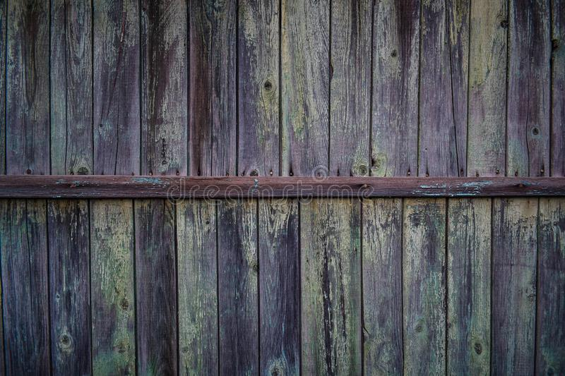 Background with the texture of the wooden wall. Of old wood with peeling paint. vintage texture of an old wooden wall with a batten in the middle, covered with stock photography