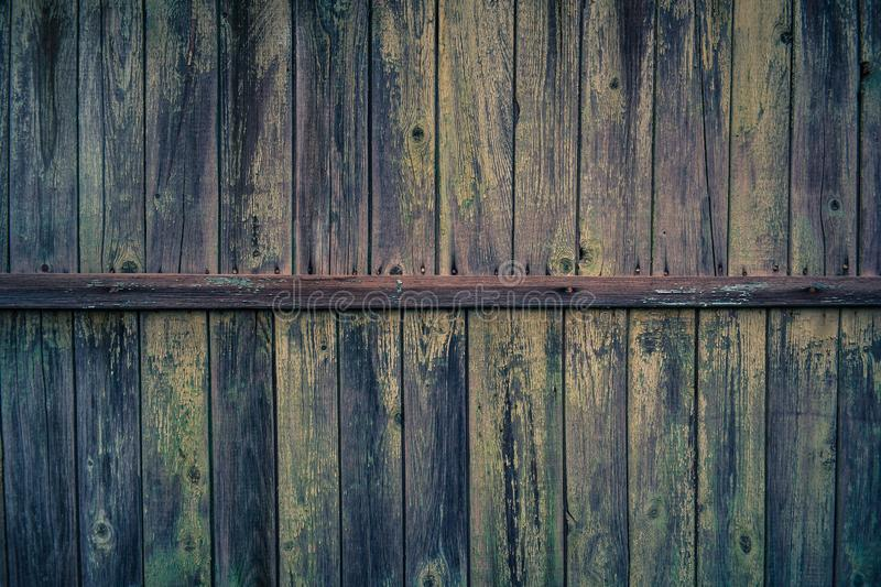 Background with the texture of the wooden wall. Of old wood with peeling paint. vintage texture of an old wooden wall with a batten in the middle, covered with royalty free stock images