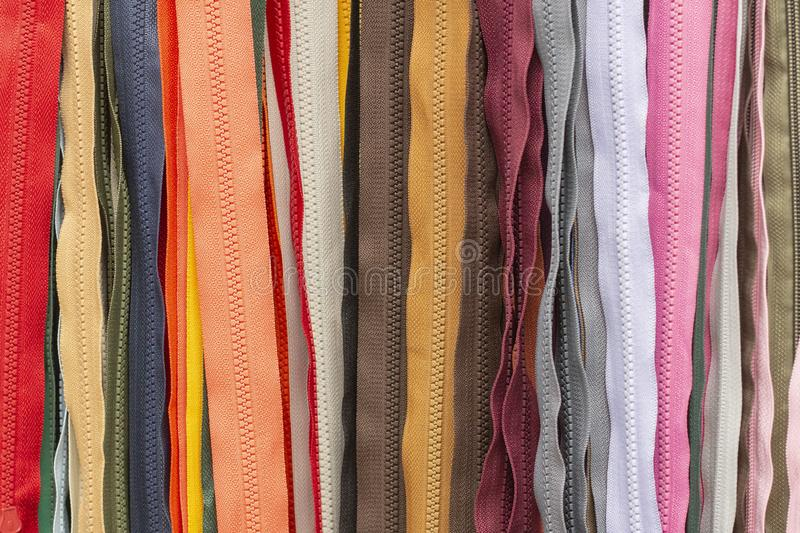 Background texture of zippers. a lot of zippers in different colors. vertical lines. Sewing clothes, atelier, fabric and accessories shop royalty free stock photos