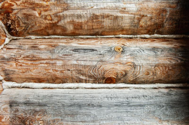 Background Textured wooden oak beams are warmed with towels in an old house. Warming of living space from logs.  stock photography