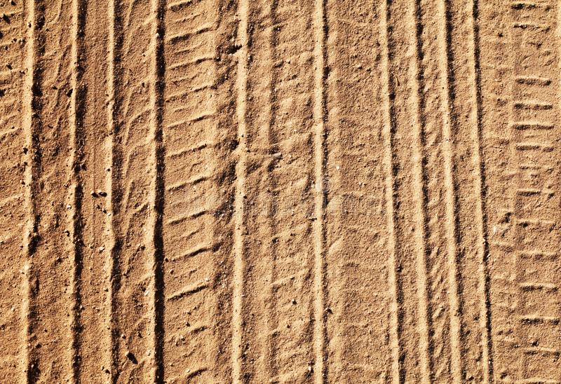 Background with tire tracks on a sandy road stock photography
