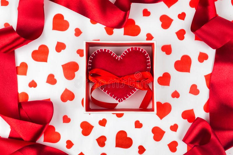 Background to Valentine`s Day or romantic event. heart in the gift box against the background of the hearts. Red ribbon stock images