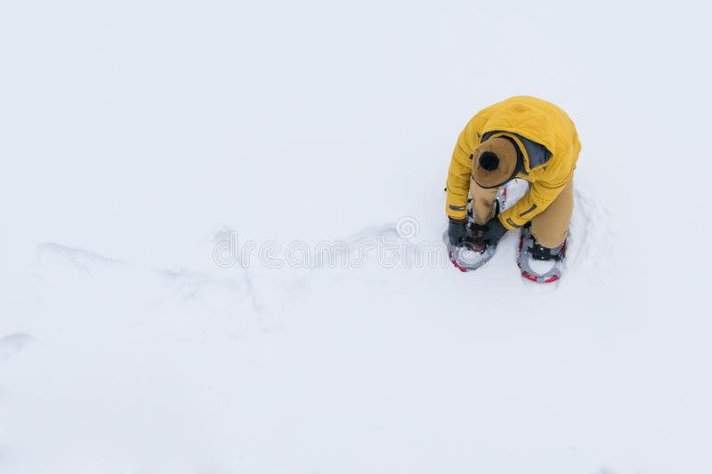 background, top view, man in the snow in a yellow jacket, wearing snowshoes to survive and pass on stock images