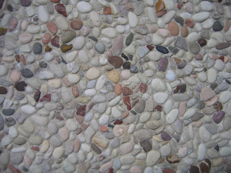 Background type view of small rocks on a pavement road. Small Stone Background stock photo