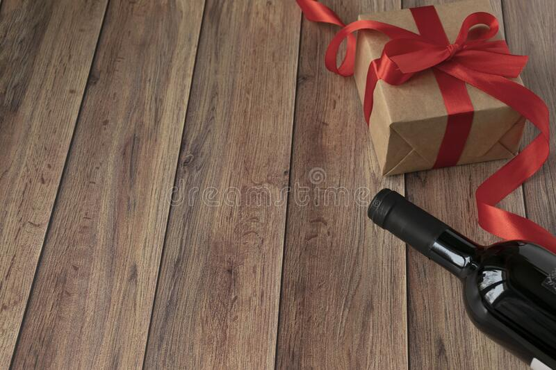 Background for Valentine`s Day. A bottle of wine, a gift from kraft paper, a heart and a satin red ribbon on a wooden background royalty free stock photo