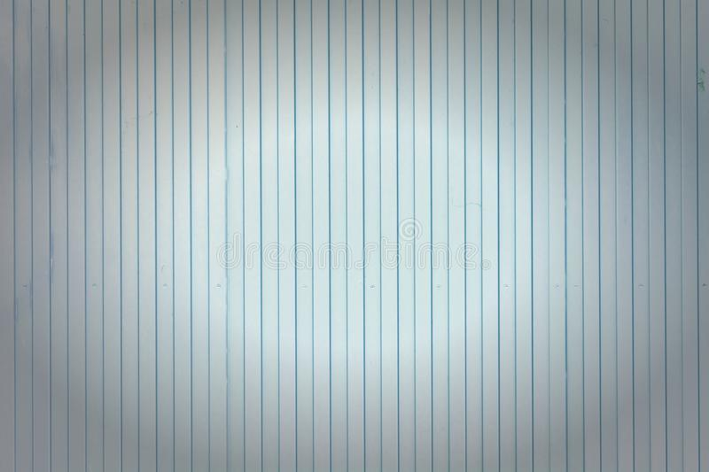 Background of vertical lines of lines. Pale blue wall of unusual stripes, laths. Photo with a vignette. royalty free stock photography