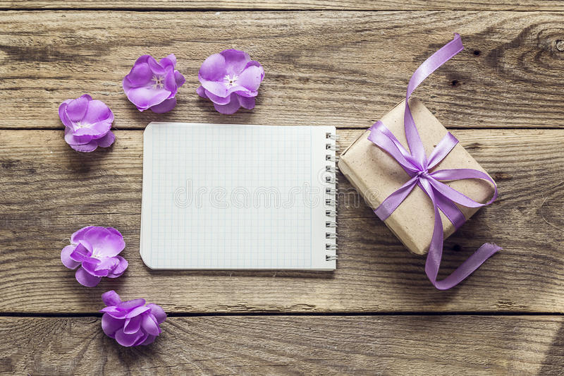 Background with violet flowers, gift box and empty notebook for. Text on wooden desks. Place for text. Top view with copy space royalty free stock image
