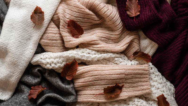 Background with warm sweaters. Pile of knitted clothes with autumn leaves, space for text, Autumn winter concept. Copy Space. Background with warm sweaters royalty free stock photos