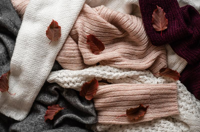 Background with warm sweaters. Pile of knitted clothes with autumn leaves, space for text, Autumn winter concept. Copy Space. Background with warm sweaters stock images