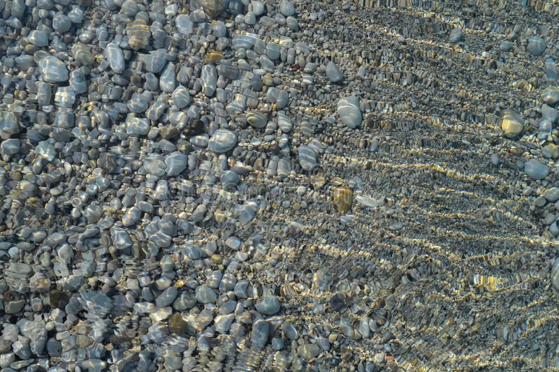 Background water, surface of sea on rocks, close up. Reflection of sun beams in water and shallow soil, shoal of ocean. Top view stock images