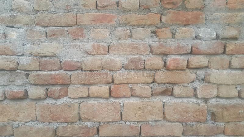 A background of a weathered old exterior brick wall in the sunshine. Closeup texture of red brick wall. A background of a weathered old exterior brick wall in stock images
