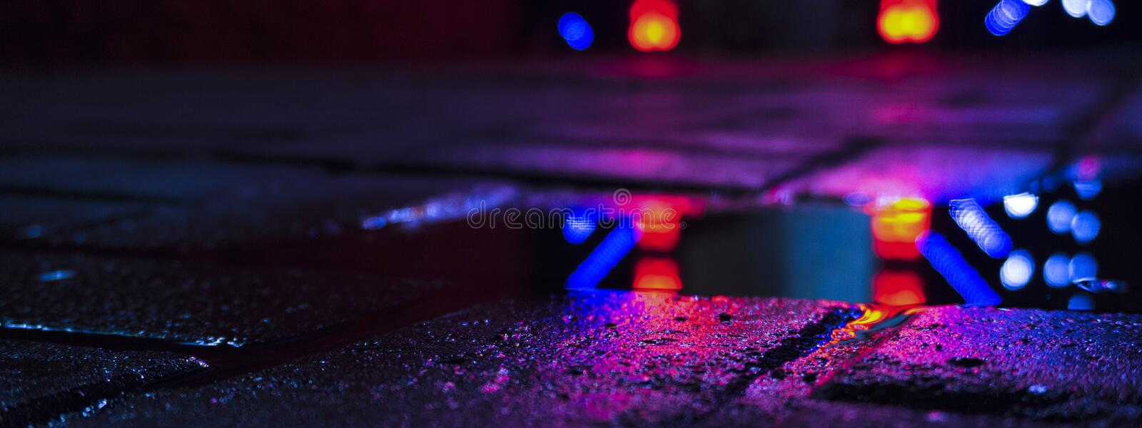 Background of wet asphalt with neon light. Blurred background, night lights of a big city, reflection, puddles. Dark neon bokeh royalty free stock image