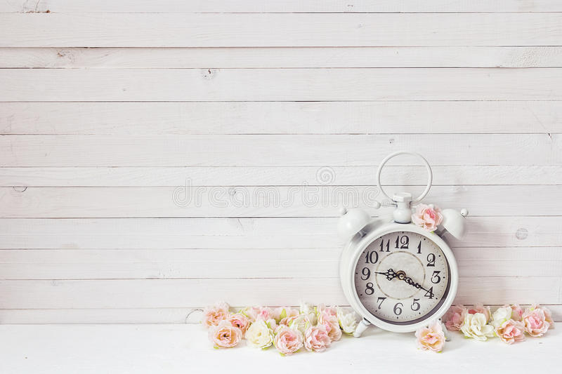 Background with white alarm clock and small pink roses on white. Painted wooden planks. Place for text stock photography