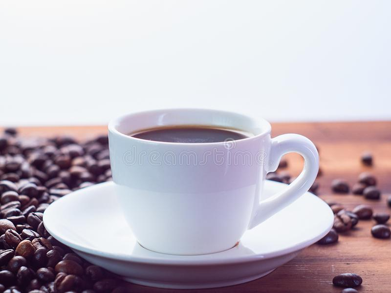 Background of white coffee cup with espresso on brown table, close up view. Roasted coffee beans pilled on brown desk. Selective soft focus. Blurred background stock images