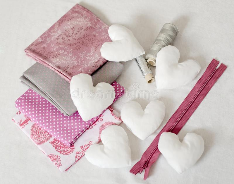 Background of white handmade textile hearts and sewing tools and accessories in pink. - image. Background of white handmade textile hearts and sewing tools and stock images