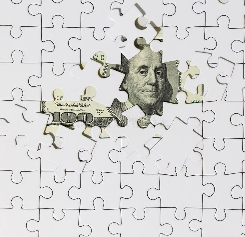 Background of white puzzle in center of which the banknote in 100 dollars royalty free stock image