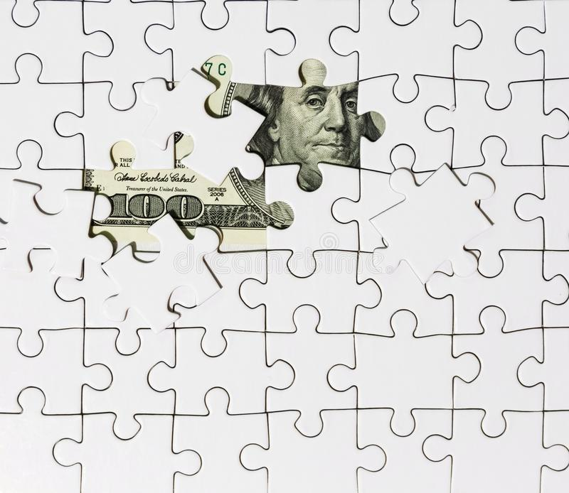 Background of white puzzle in center of which the banknote in 100 dollars stock image