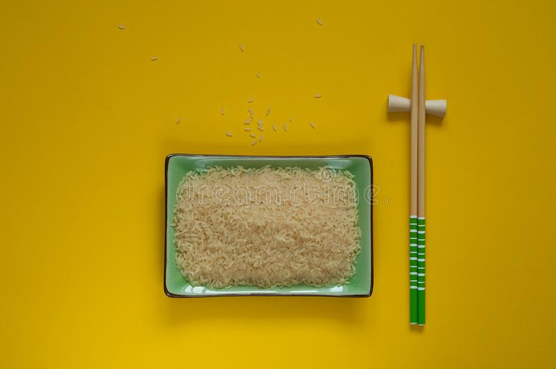 Background of white rice in a green bowl with chopsticks, isolated on a bright yellow texture. Asian food, copy space, top view royalty free stock photos