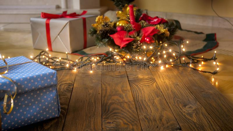 Beautiful background with wooden boards against glowing Christmas lights, gift boxes and baubles. Perfect for winter royalty free stock images