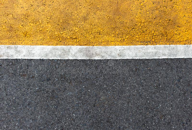 Background of yellow black strips . Dark grey asphalt road divided by yellow paint stock photos