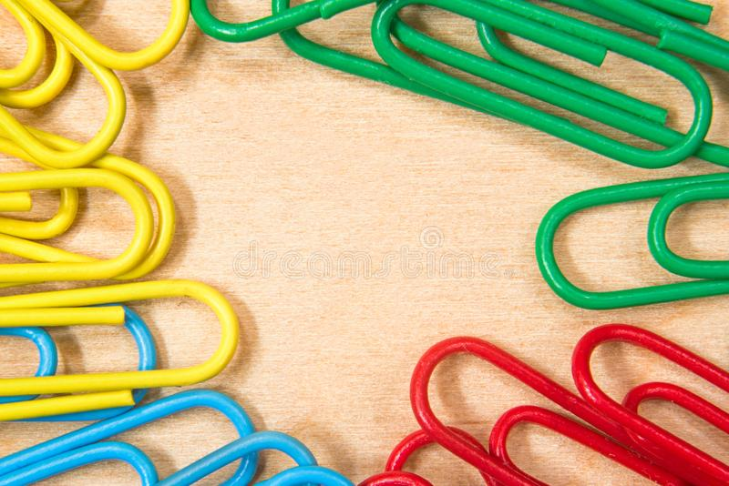 Background of yellow, blue, green, red paper clips on a wooden surface macro. Background of yellow, blue, green, red paper clips on a wooden surface close royalty free stock images