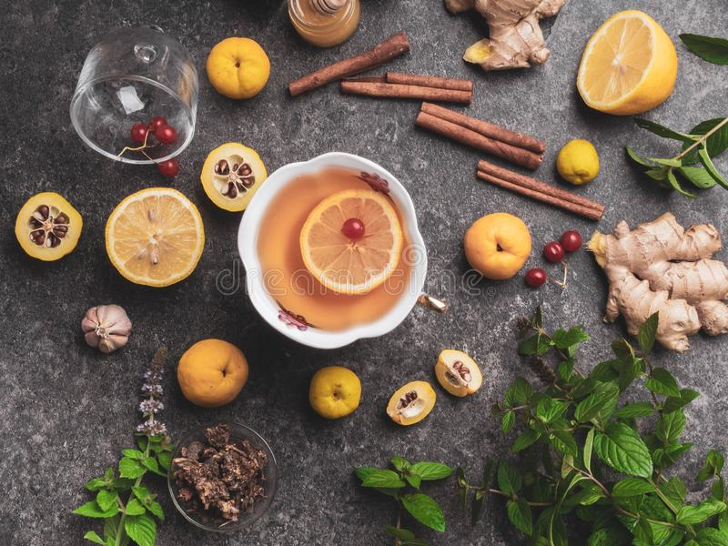 Cup of ginger tea with lemon, cranberry, different honey in jars, cydonia, cinnamon sticks on concrete background, Hot winter stock images
