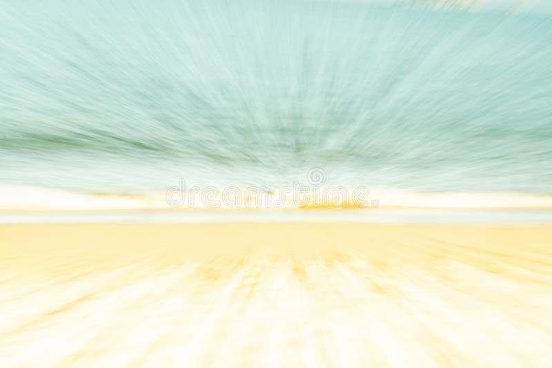 Backgrounds soft hues coastal abstract. Golden sand blue water and pale sky in zoom blur stock image