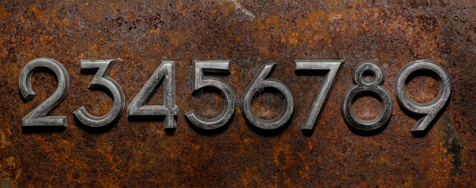Row of metal cyrillic digits on a rusty background stock photos