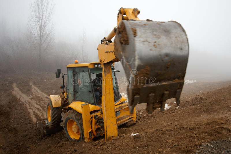 Backhoe. Excavator Loader with backhoe rised standing on earth royalty free stock images