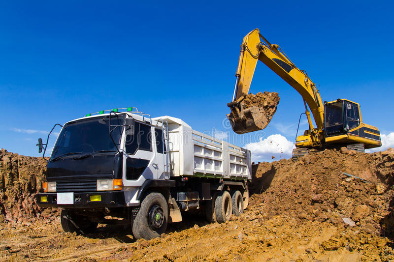 Backhoe digging and trucks. stock photo